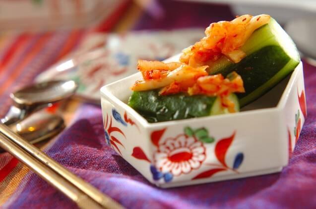 テーブルの上、四角い器に盛られたきゅうりと白菜キムチの即席オイキムチ