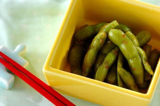 ほんのりしょうゆ色になった枝豆のにんにくしょうゆ煮が盛られた小皿とお箸