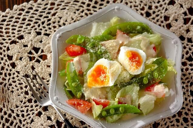 六角形の白皿に盛られた、スナップえんどうとトマト、ポーチドエッグのシーザーサラダ