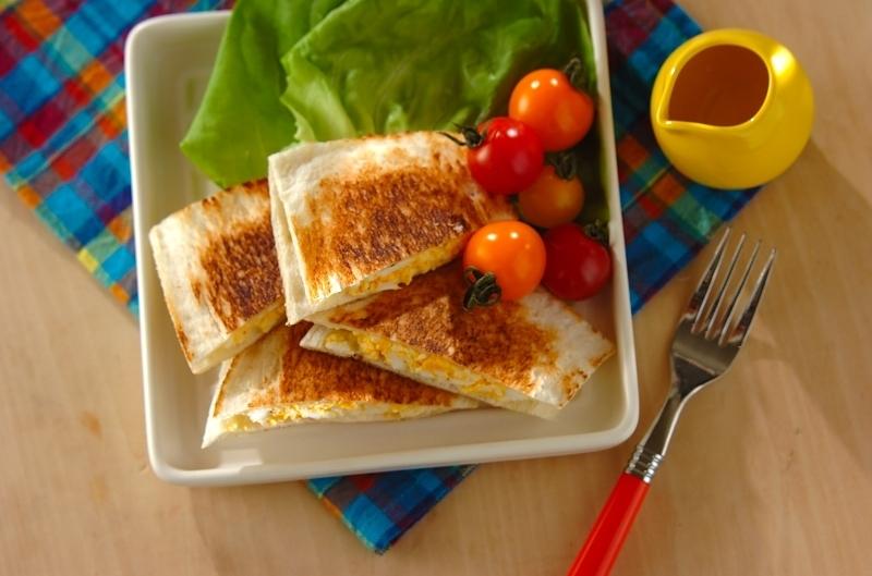 お皿に野菜と盛り付けられた表面が香ばしく焼かれたホットサンドイッチ