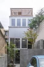 傾斜地につくった塔状の家アウトドア気分のリビングは擁壁に囲まれた吹き抜け空間