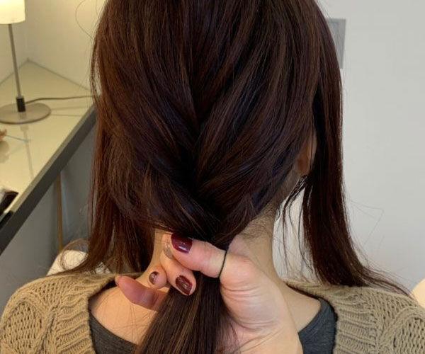 両サイドを少しずつ残し、三つ編みにした部分も一緒に髪を後ろでまとめて結びます。