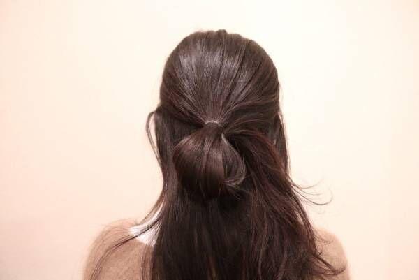 耳上の髪をハーフアップにして、ゴムで留めるとき、最後を抜ききらずにお団子にします。