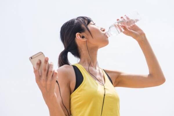 ペットボトルのお水を飲む女性