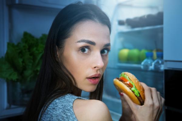 冷蔵庫の前で間食しようとする女性