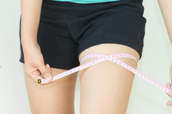 太ももの太さを測る女性