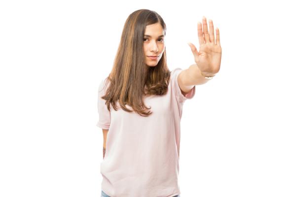 手のひらを前に向けて注意のサインをする女性