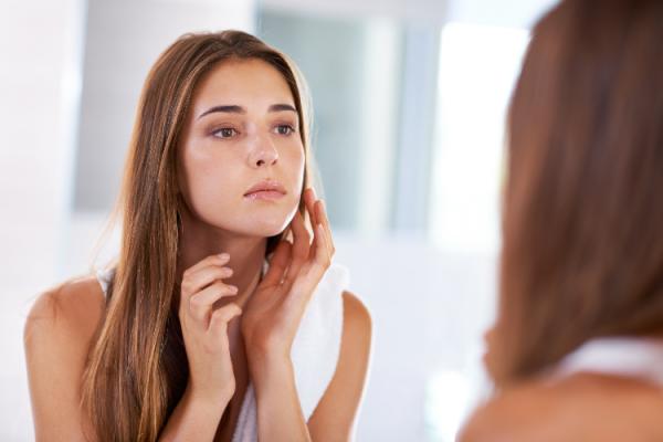 鏡で肌の調子を確認する女性