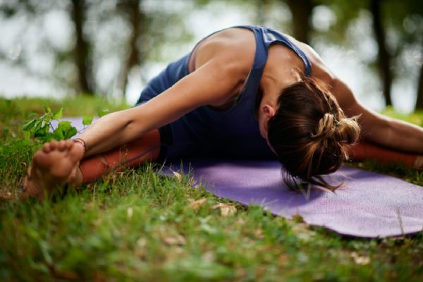芝生の上で開脚前屈をする女性