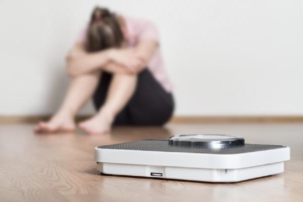 体重計の前で落ち込む女性