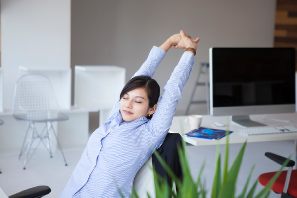 オフィスで上半身を伸ばす女性
