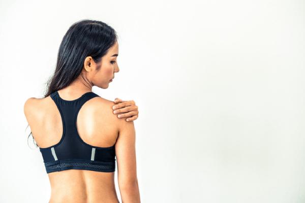 スポーツウェアを着て肩を押さえる女性の後ろ姿