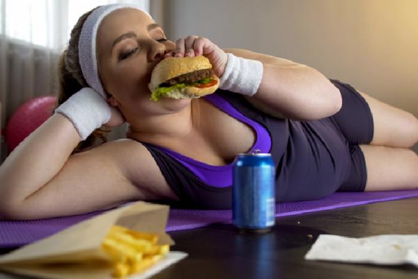 スポーツウェアを着てハンバーガーを食べる女性