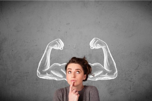 筋肉質な腕の絵を背景に何かを考える女性