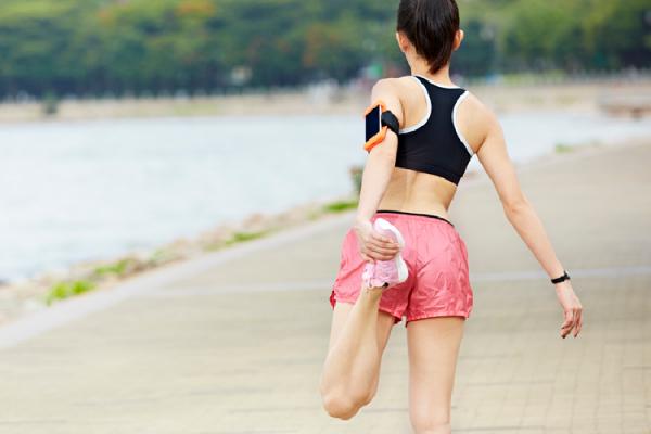 運動前に足を伸ばす女性