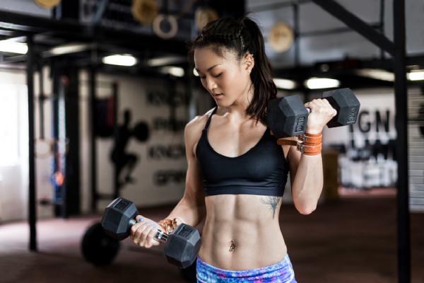 ダンベルを使ってトレーニングする女性