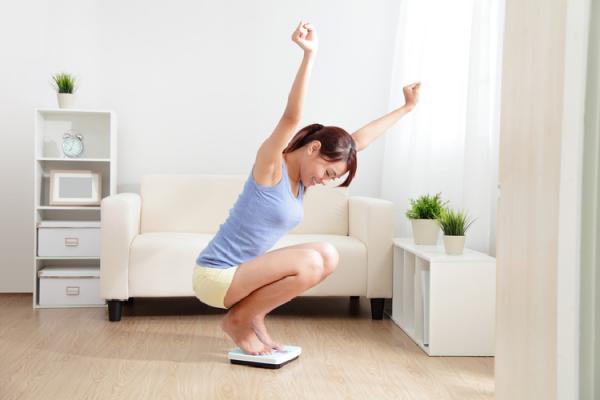 体重計の上で喜びを表現する女性