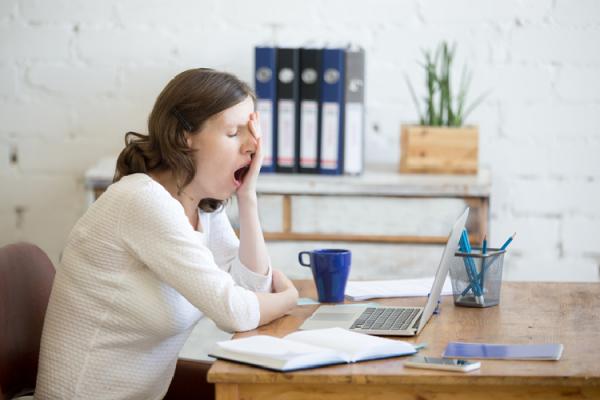 パソコンの前であくびをする女性