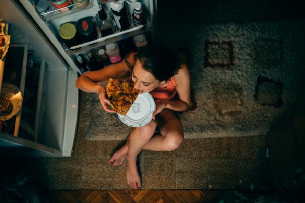 冷蔵庫の前でピザをかじる女性