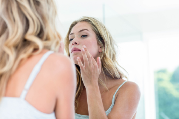 鏡で表情を確認する女性