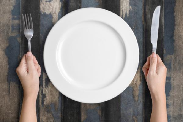 空の皿とフォーク・ナイフを持つ手元