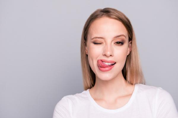 ペコちゃんのように舌を出す女性