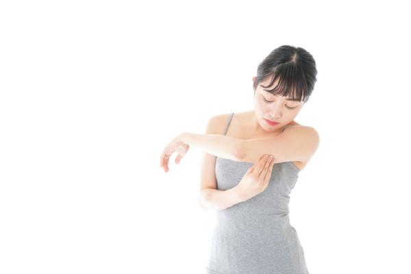 腕の脂肪をつまむ女性