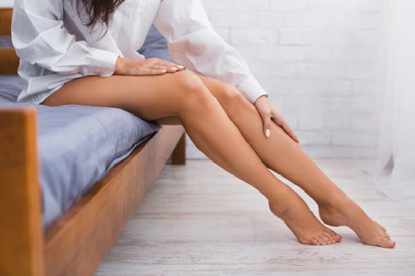 ベッドに腰をかける女性の綺麗な脚