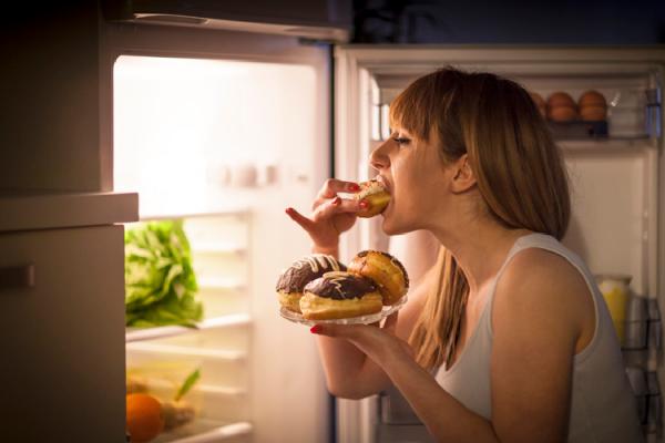 冷蔵庫の前でドーナツを頬張る女性
