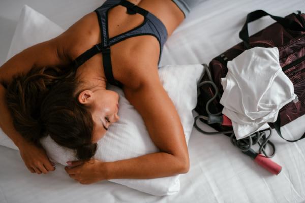 ヨガの後にベッドに倒れこむ女性