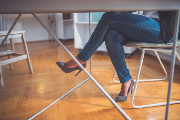 テーブルの下で脚を組む様子