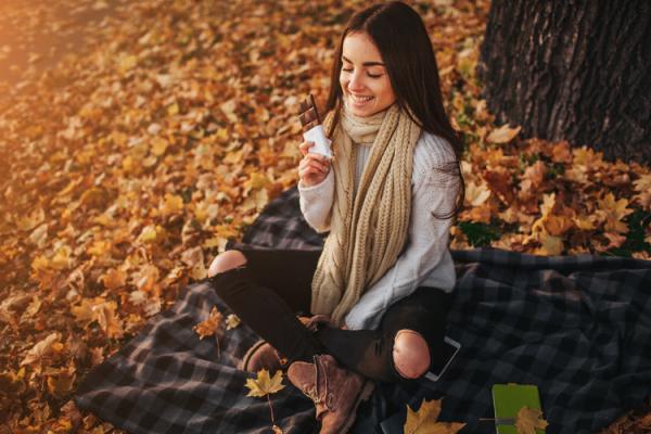 秋空の下でチョコを食べる女性