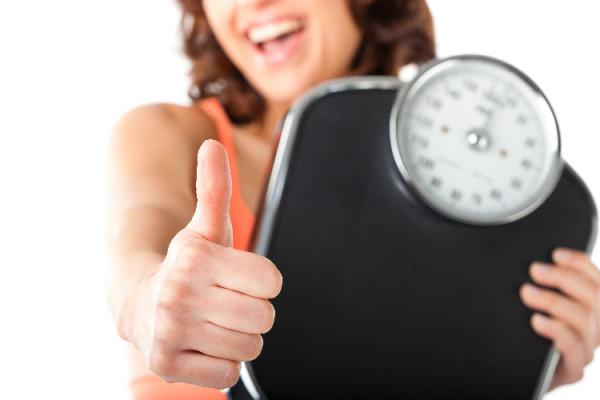 体重計を持って喜ぶ女性