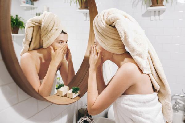 鏡を見てマッサージをする女性