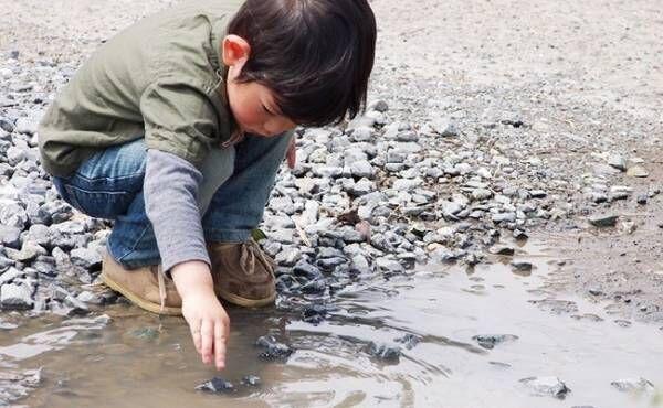 水溜まりで遊ぶ男の子