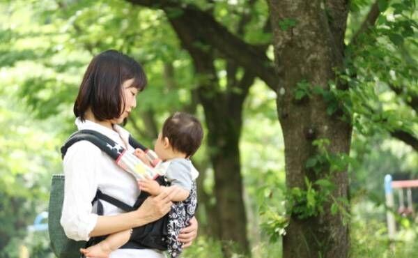 抱っこ紐でお出かけ中の赤ちゃんとママのイメージ
