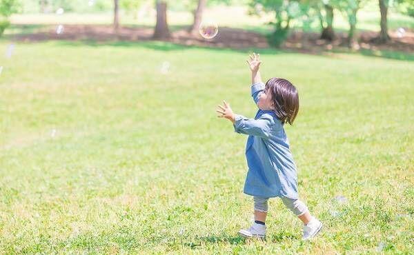 しゃぼん玉を追いかける女児