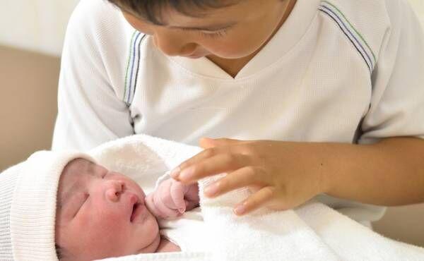 新生児を抱っこする男児