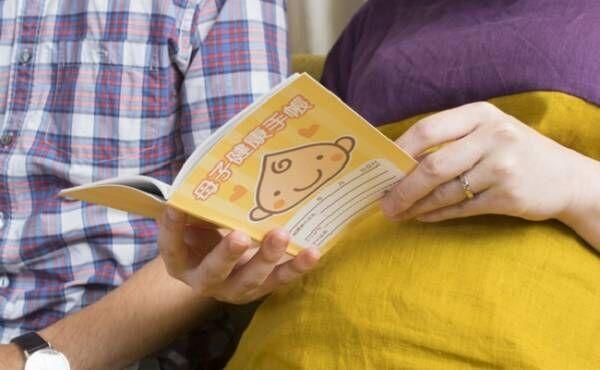 母子手帳を見ている夫婦のイメージ