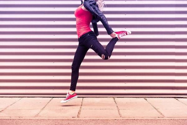 Young happy woman jumping in front of metal wall 2 free stock photos picjumbo dsc03711 1570x1047