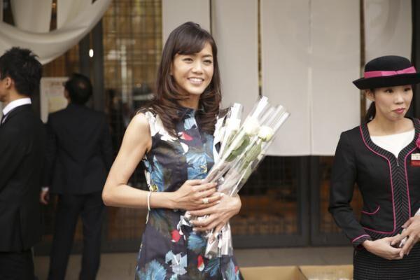 来店客に花を渡す前田典子さん
