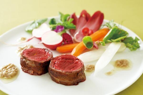 岩田シェフ直伝の「鹿ロース肉の塩豚巻き」(作り方:1.鹿ロース肉250gに塩豚バラスライス50gを巻き付けて、数カ所をたこ糸で縛り、全体に黒胡椒をまぶす。2.オリーブオイルを入れて熱したフライパンに1.を加え、均等に火が通るように向きを変えながらきつね色になるまで焼き上げる。3.2を輪切りにして季節の野菜と共に盛りつけ、温めたバーニャカウダソースを添える)