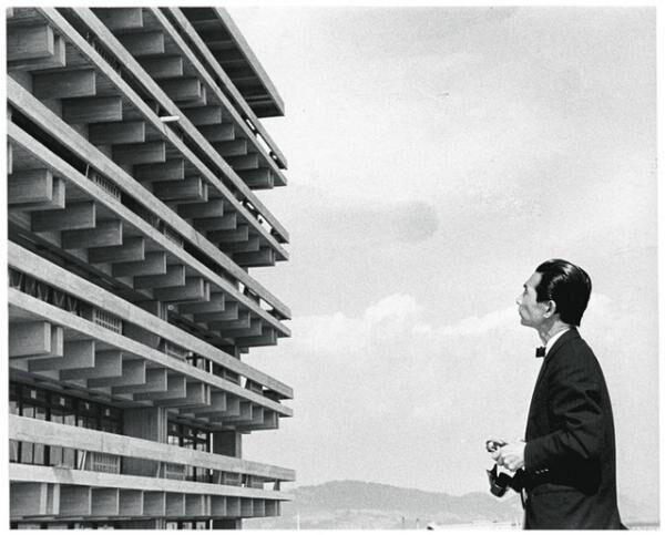 カメラを手に竣工当時の香川県庁舎と対峙する丹下 1958 年頃撮影 撮影者不明