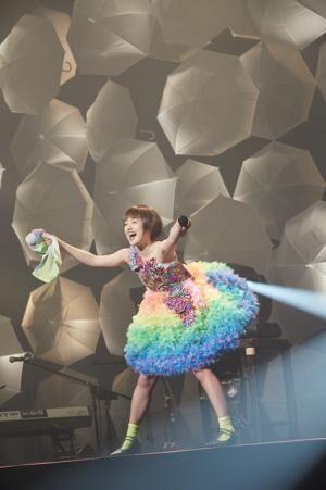 虹色の衣装でステージに立つ武藤彩未