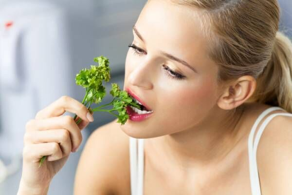 Young woman eating coriander at domestic kitchen