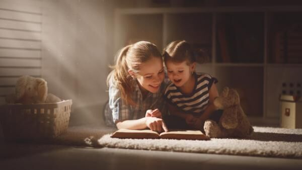 happy family mother and daughter read a book in evening