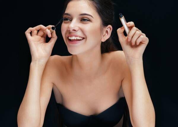 Beautiful young woman with mascara brush.