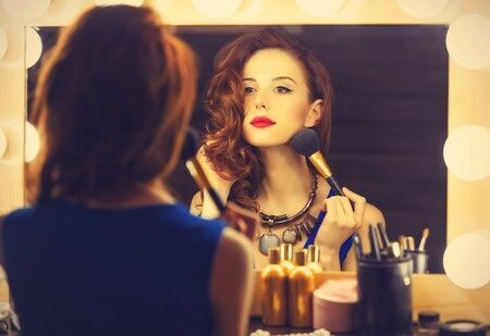 35369884 - portrait of a beautiful woman as applying makeup near a mirror. photo in retro color style.