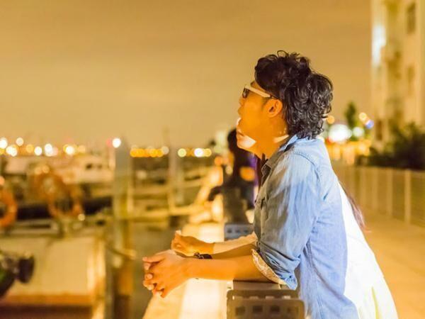 Japanese couple looking far away at wharf