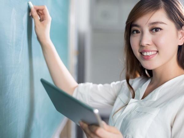 asian beautiful woman writing on blackboard with tablet